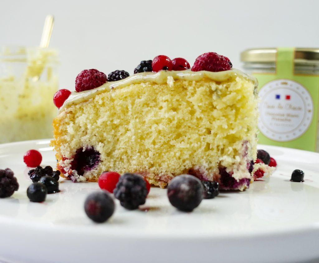 Gâteau moelleux au yaourt, fruits rouges et nappage à la pâte à tartiner au chocolat blanc pistache.