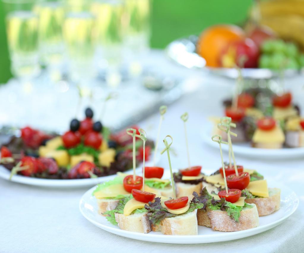 Table avec des brochettes salés composées de fromages, pain, fruits, salades et tomates.